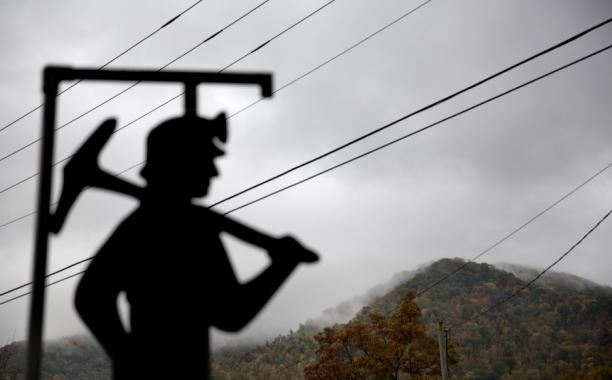 Fog hovers over a mountaintop as a cutout depicting a coal miner stands at a memorial to local miners killed on the job in Cumberland, Ky. (AP Photo/David Goldman, File)