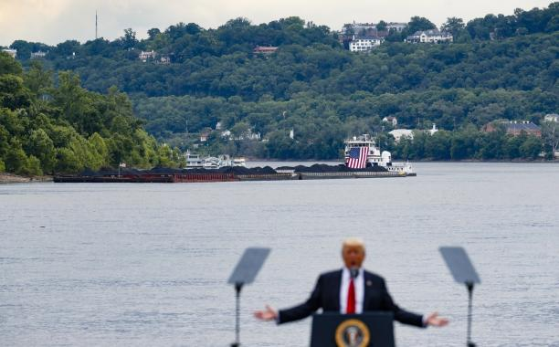 In this June 7, 2017 file photo, a coal barge is positioned as a backdrop behind President Donald Trump as he speaks during a rally at the Rivertowne Marina in Cincinnati. President Donald Trump personally promised to activate emergency legal authorities to keep dirty or economically uncompetitive coal plants from shutting down, a top American coal company said. The Trump administration now says it has no plans to do so. (John Minchillo, File/Associated Press)