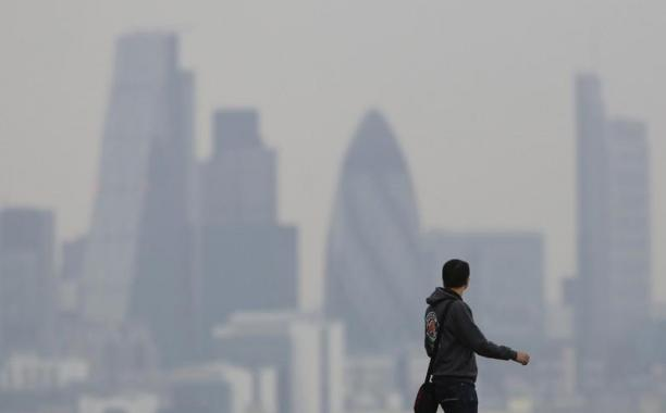 FILE PHOTO - A man walks through Greenwich Park as a haze of pollution sits over the London skyline April 3, 2014. REUTERS/Luke MacGregor